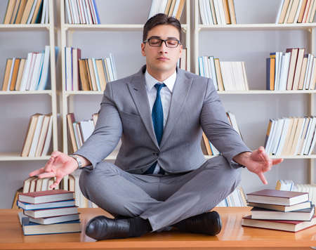 Businessman student in lotus position concentrating in the libr Imagens - 133381179