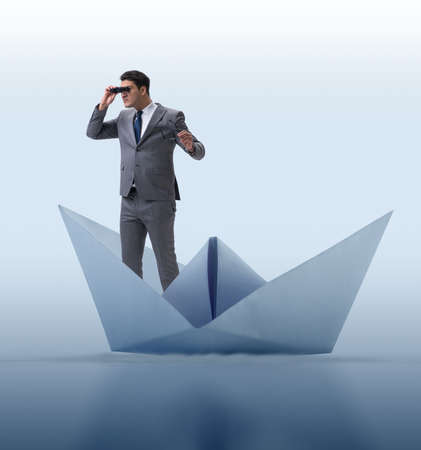 Businessman looking into future with binoculars in paper ship bo Banque d'images - 132766801