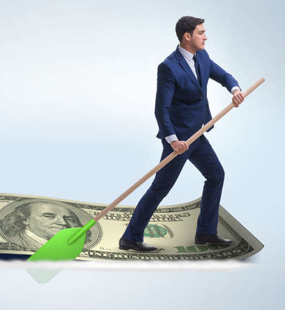 The businessman rowing on dollar boat in business financial conc Banque d'images - 132766756