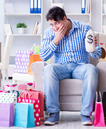 The young man after excessive shopping at home Stock Photo