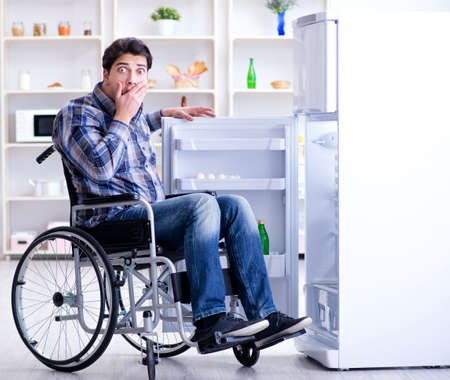 Young disabled injured man opening the fridge door Stockfoto