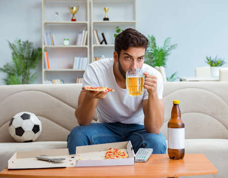 Man eating pizza having a takeaway at home relaxing resting Stock Photo
