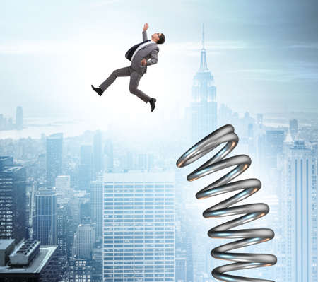 Businessman jumping from spring in promotion concept Banco de Imagens