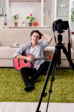 Young guitar player recording video for his blog 写真素材
