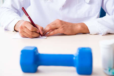 The young male doctor in sport and dieting concept