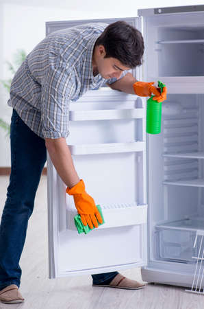 Man cleaning fridge in hygiene concept