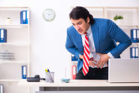 Young male employee suffering in the office