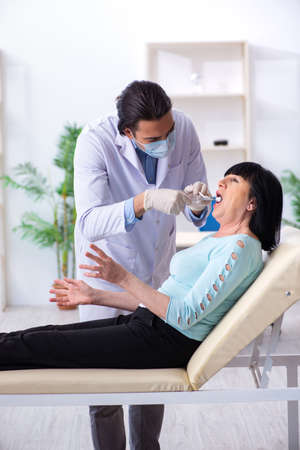 Old woman visiting young doctor dentist Standard-Bild