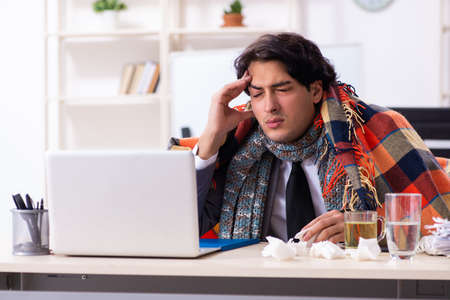Man with flu working in the office Stock Photo