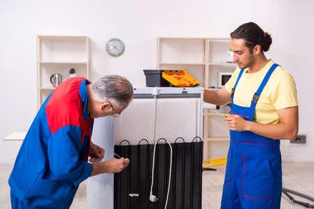 Dwóch wykonawców naprawiających lodówkę w warsztacie