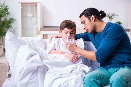 Young father caring for sick son Stock Photo