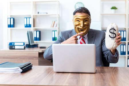 Businessman wearing mask in hypocrisy concept Foto de archivo