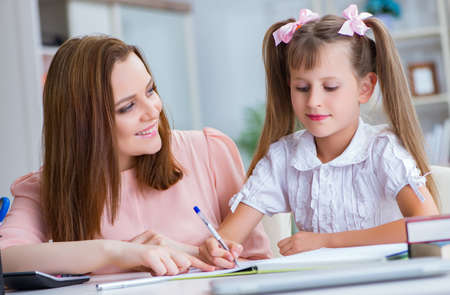 Mother helping her daughter to do homework Imagens