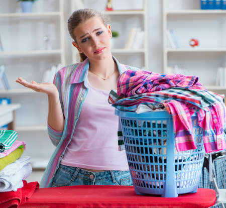 Tired depressed housewife doing laundry Фото со стока - 133684004