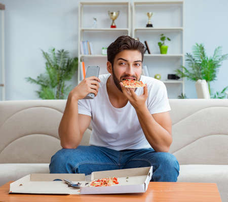 Man eating pizza having a takeaway at home relaxing resting Archivio Fotografico - 133684013