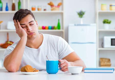 El hombre se queda dormido durante su desayuno después del trabajo de horas extraordinarias