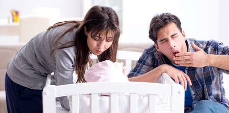 The young parents with their newborn baby near bed cot