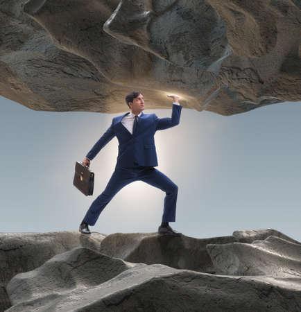 Businessman supporting stone under pressure Reklamní fotografie
