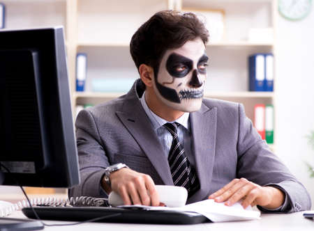 Businessmsn with scary face mask working in office 写真素材