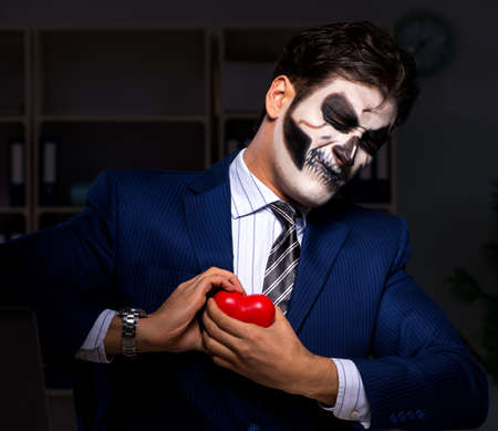 The businessman with scary face mask working late in office