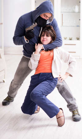The armed man assaulting young woman at home Reklamní fotografie