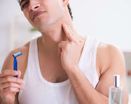 Young handsome man shaving early in the morning at home Standard-Bild