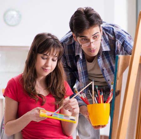 Artist coaching student in painting class in studio