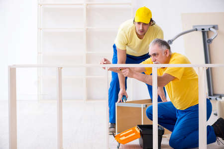 Zwei Bauunternehmer, die im Innenbereich arbeiten Standard-Bild