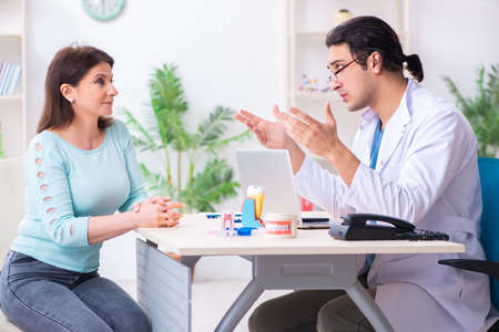 Middle-aged woman visiting male doctor stomatologist