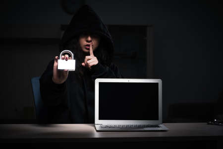 Female hacker hacking security firewall late in office 스톡 콘텐츠