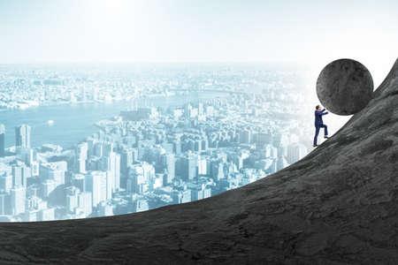 Man pushing large stone to the top