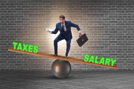 Businessman balancing between taxes and salary Stock Photo