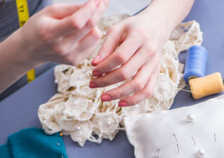 Woman tailor working on a clothing sewing stitching measuring fabric