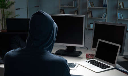 The hacker hacking computer at night