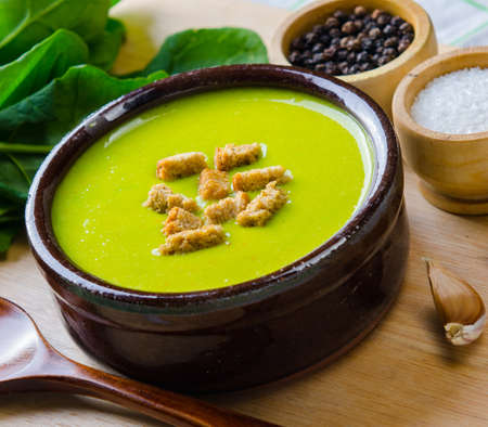 The spinach soup served on wooden board