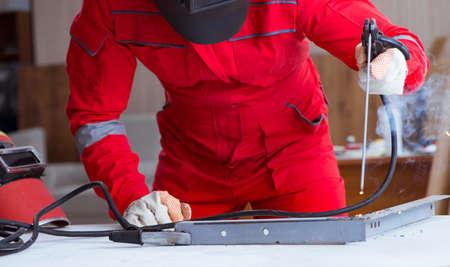Young repairman with a welding gun electrode and a helmet welding metal