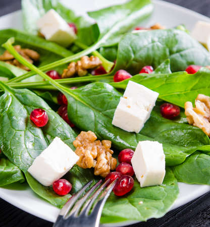 The spinach salad with nuts and apples served on table 스톡 콘텐츠