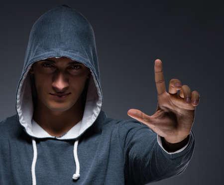 Jeune homme portant un sweat à capuche en appuyant sur des boutons virtuels Banque d'images