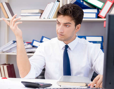 Businessman working in the office with piles of books and papers