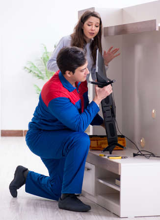 Tv repairman technician repairing tv at home