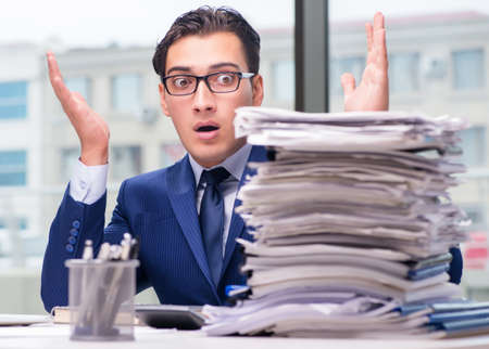 Workaholic businessman overworked with too much work in office Stock Photo