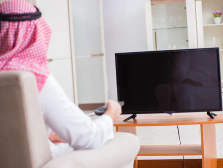 Arab businessman watching tv at home
