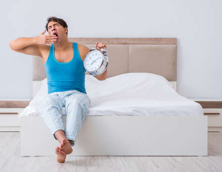 Young man waking up in bed Stock Photo