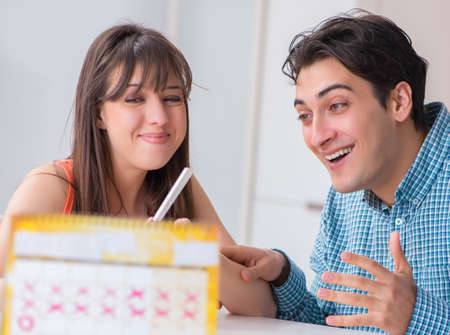 Young family in pregnancy planning concept with ovulation calend