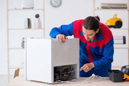 Young male contractor repairing refrigerator at workshop