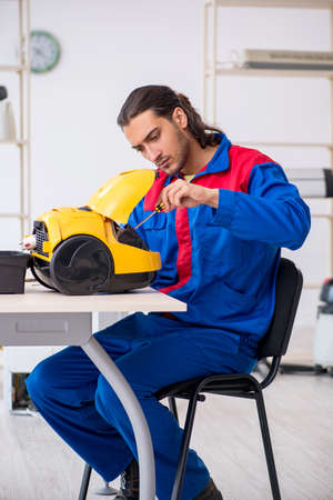 Young male contractor repairing vacuum cleaner at workshop Foto de archivo - 134287448