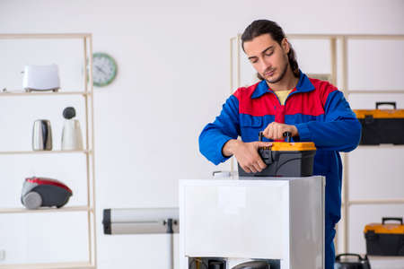 Young male contractor repairing refrigerator at workshop Фото со стока