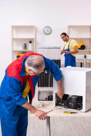 Two contractors repairing fridge at workshop Stockfoto