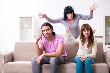 Junge Familie und Schwiegermutter in Familienangelegenheiten Konzept Standard-Bild