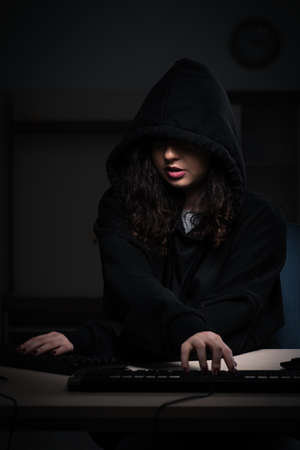 Female hacker hacking security firewall late in office 免版税图像